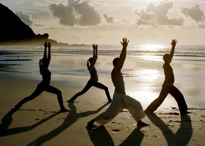 Persone che fanno yoga in spiaggia